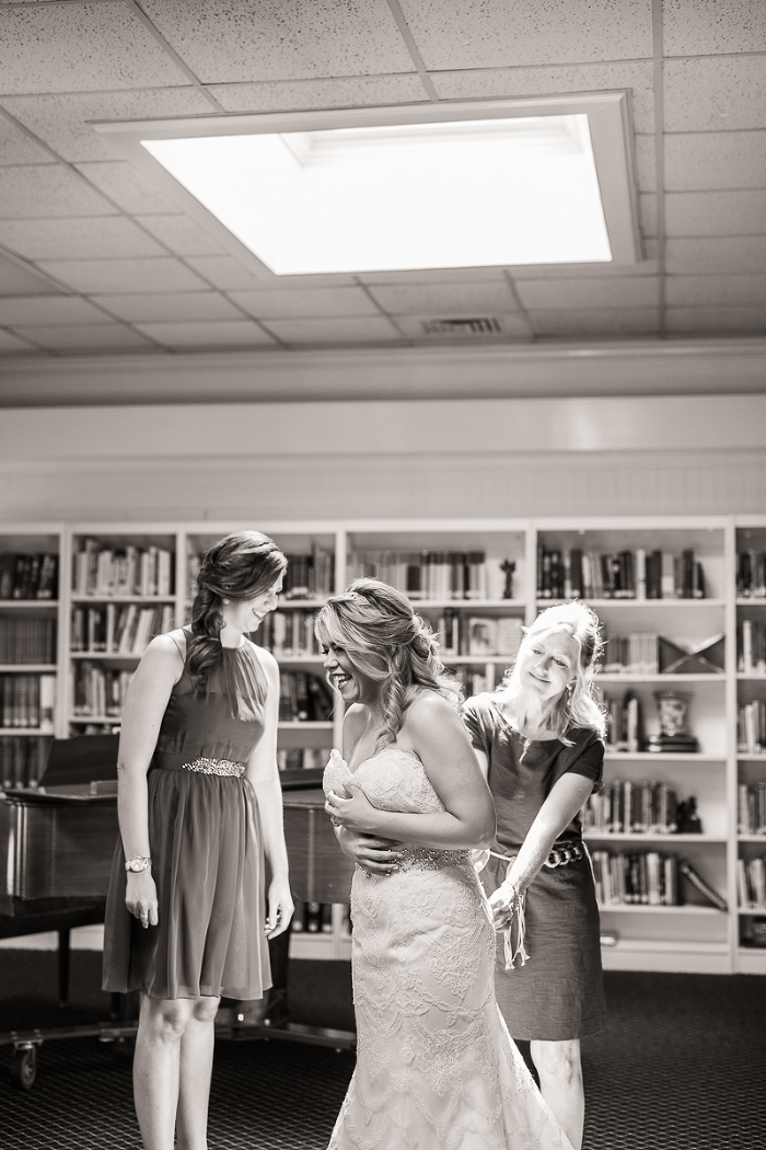 Gardens at Great Oaks Columbus Georgia Bride Putting on Lace Dress Curled Hair Black and White Wedding Photo | www.hannahandrandall.com